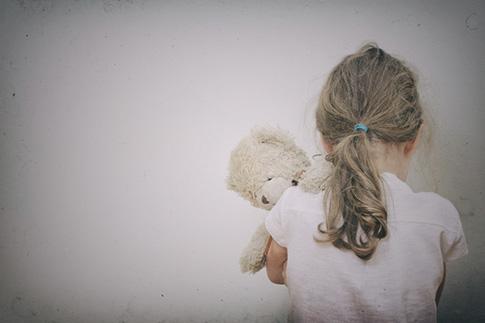 child hugging teddy bear